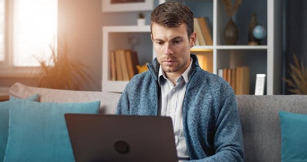 Uomo consumato utilizzando laptop tenendolo in grembo seduto sul divano in appartamento, e-lavoro, diversione