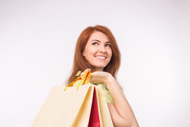 Concetto di consumatore, vendita e persone. donna della testarossa di stile che tiene i sacchetti della spesa