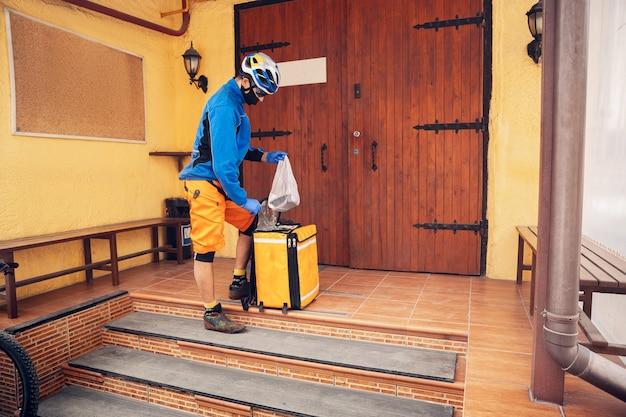 Servizio di consegna contactless durante la quarantena. l'uomo consegna cibo e borse della spesa durante l'isolamento. bussa alla porta e lascia la merce finché il cliente non la prende. sicurezza, ricezione, distanza.