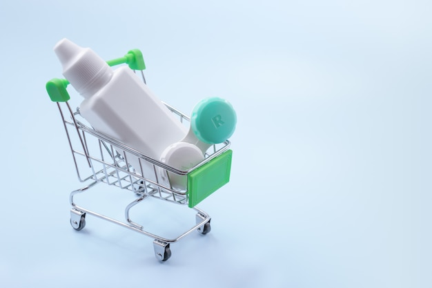 Lenti a contatto e liquido per lenti nel carrello della spesa. concetto di acquisto di lenti a contatto.