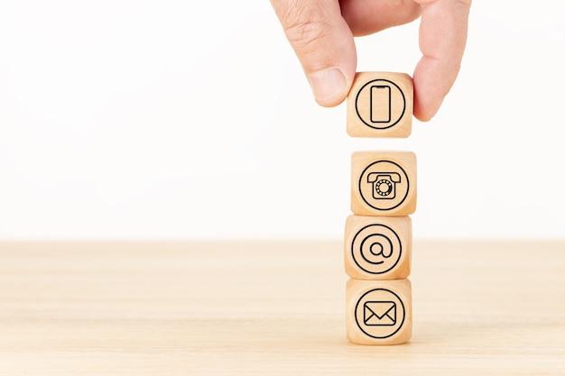 Contattaci in background. pagina del sito web. mano che tiene un blocco di legno e blocchi impilati con icone di contatto. copia spazio.