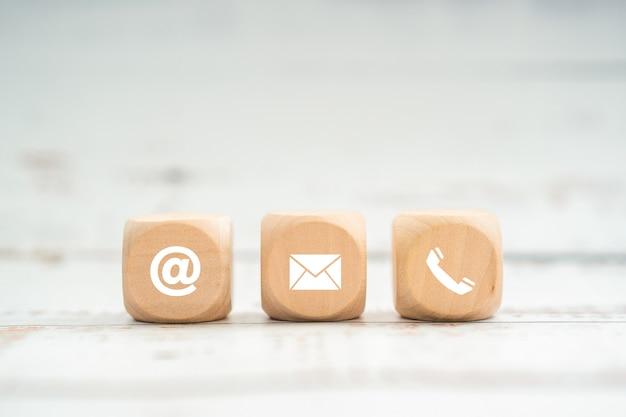Contattaci icona (telefono, email, posta) su cubo di legno, servizio di assistenza clienti