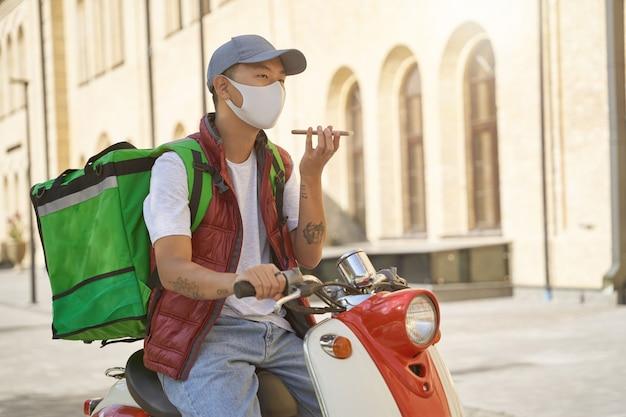 Consegna senza contatto durante la quarantena giovane corriere maschio asiatico con borsa termica che indossa il viso