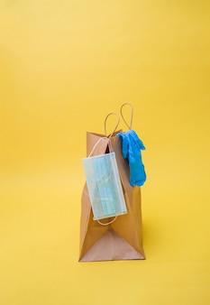 Consegna senza contatto un sacchetto di carta con una maschera monouso e guanti su uno spazio giallo. guanti blu e una maschera blu.