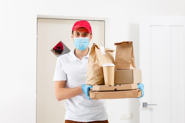 Consegna pizza senza contatto. scatola della pizza. fattorino che tiene scatole di cartone in guanti di gomma medica e maschera. trasporto di consegna veloce e gratuito. acquisti online e consegna espressa. quarantena