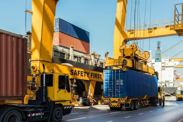 Nave mercantile del carico del contenitore con il ponte di caricamento funzionante della gru in cantiere navale al crepuscolo per il fondo logistico dell'esportazione dell'importazione