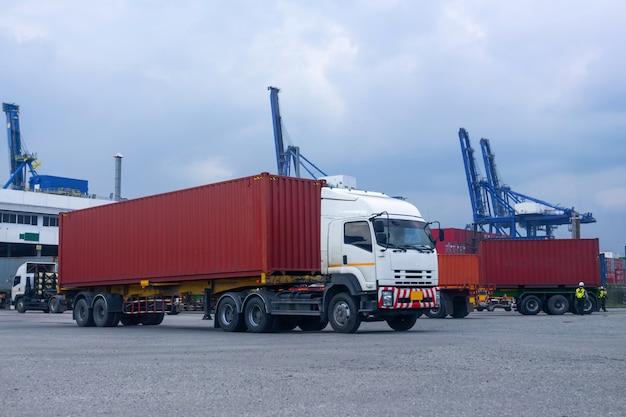 Camion rosso del contenitore nel porto logistico della nave