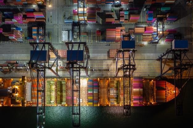 Carico di navi portacontainer e u nel porto d'altura, vista aerea del servizio alle imprese e importazione logistica di merci industriali ed esportazione di trasporto merci tramite nave porta-container in mare aperto,