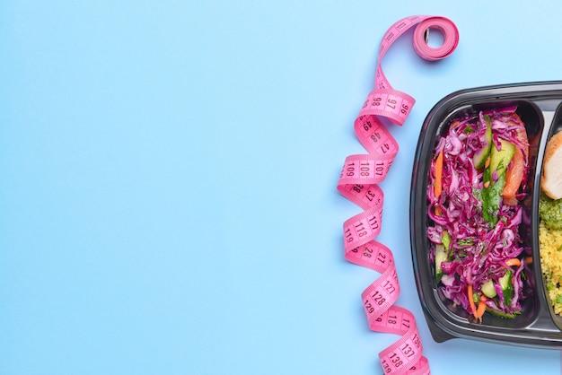 Contenitore con cibo sano e metro a nastro sul colore