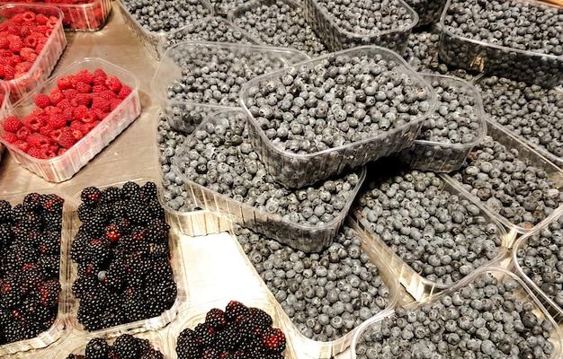 Contenitori con diversi frutti di bosco freschi maturi e mercato di frutta.
