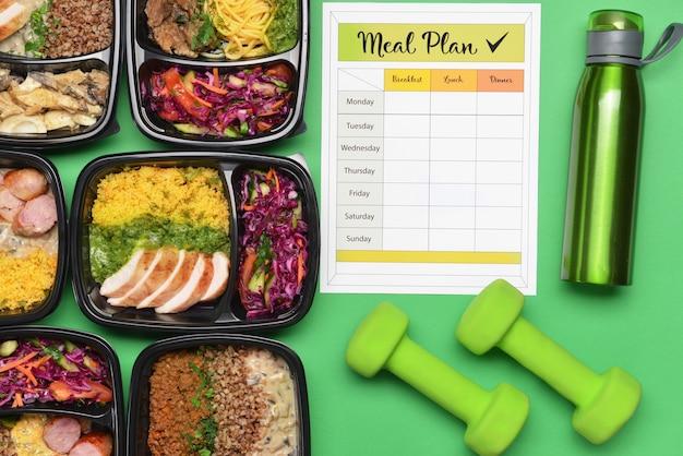 Contenitori con cibo sano, bottiglia d'acqua, manubri e programma alimentare sul colore