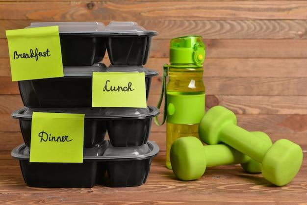 Contenitori con cibo sano, bottiglia d'acqua e manubri su legno
