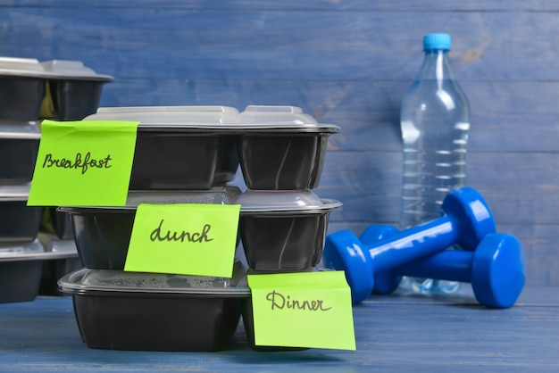 Contenitori con cibo sano, manubri e bottiglia d'acqua sul colore
