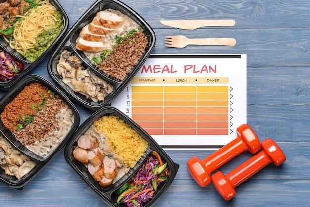 Contenitori con cibo sano, manubri e programma alimentare sul colore