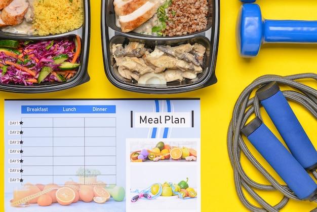 Contenitori con cibo sano, attrezzature sportive e programma alimentare sul colore