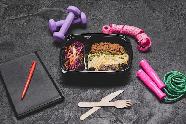 Contenitori con cibo sano, attrezzature sportive e metro a nastro su oscurità