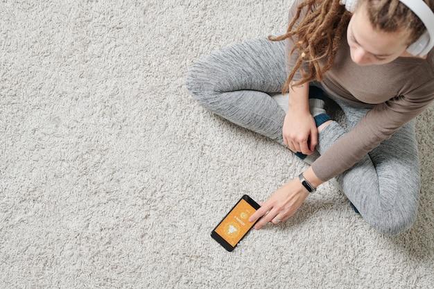 Ragazza attiva contemporanea che si siede sul pavimento e andando a guardare la sessione video di yoga in smartphone