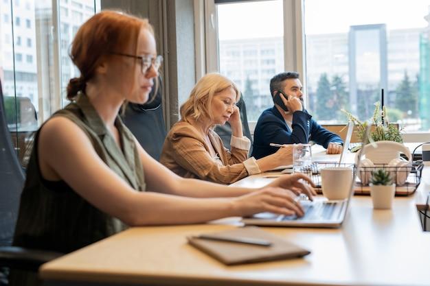 Donna di affari matura bionda contemporanea ed i suoi giovani colleghi occupati che lavorano individualmente davanti ai computer portatili in ufficio