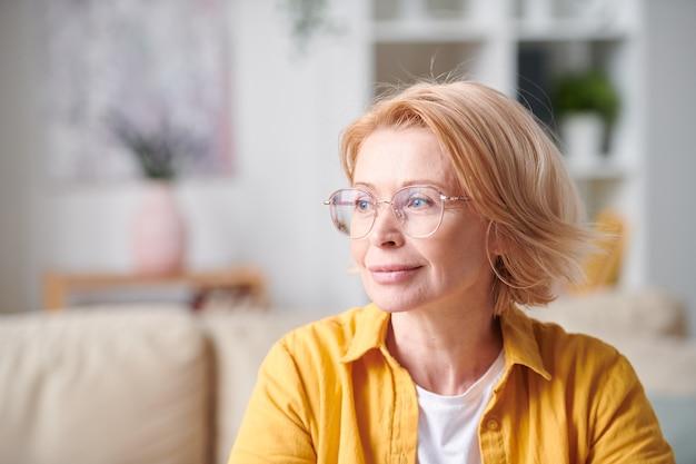 Femmina matura bionda contemporanea in abbigliamento casual giallo e occhiali da vista che esprimono serenità pur avendo riposo nell'ambiente domestico