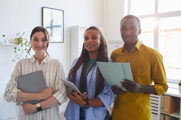 Squadra di affari contemporanea che tiene le cartelle con i documenti mentre posa in ufficio illuminato dalla luce solare