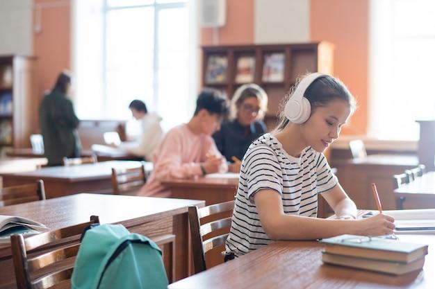Studente di college contemporaneo con le cuffie annotare il piano del seminario nel blocco note mentre era seduto in biblioteca