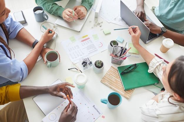 Team creativo contemporaneo che lavora insieme a un tavolo ingombra di tazze da caffè e documenti, lavoro di squadra o concetto di studio