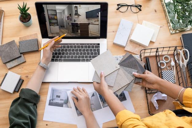 Designer contemporaneo che indica un esempio di interni domestici sul display del laptop durante la consultazione