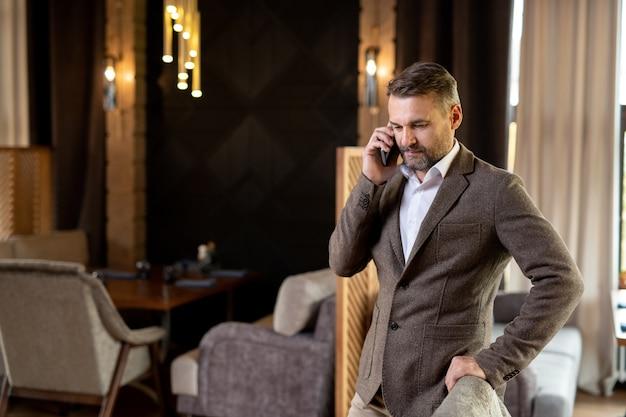 Uomo d'affari elegante contemporaneo in giacca e camicia bianca in piedi in un lussuoso ristorante mentre parla dal telefono cellulare