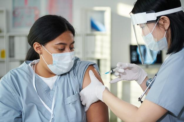 Clinica femminile contemporanea in uniforme e abbigliamento da lavoro protettivo che fa l'iniezione al suo collega di razza mista durante la vaccinazione contro il covid