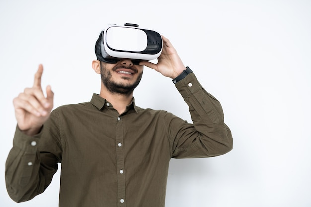 Ragazzo contemporaneo con auricolare vr che punta al display virtuale mentre si effettua o si prepara la presentazione in isolamento