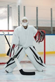 Giocatore di hockey contemporaneo in uniforme sportiva, casco protettivo e guanti che tengono il bastone mentre si trova in piedi sulla pista contro la rete e aspetta il disco