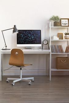 Postazione di lavoro moderna di home office con sedia in legno e pc illuminato da una calda lampada