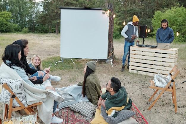 Ragazzi e ragazze interculturali contemporanei che chiacchierano all'aperto sdraiati su tappeti e cuscini mentre due uomini costruiscono giradischi nelle vicinanze