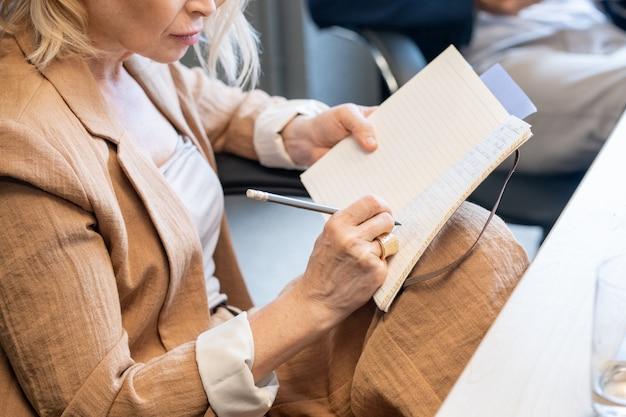 Donna di affari matura contemporanea con penna e taccuino che prende appunti di lavoro o lavoro di pianificazione mentre si siede dallo scrittorio