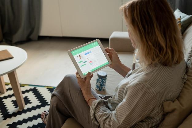 Donna matura contemporanea con la compressa che si siede sul divano in soggiorno e guardando attraverso il sito web medico o consultando il medico