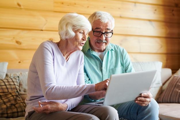 Anziani mobili contemporanei seduti sul divano nella loro casa di campagna e discutendo di notizie online nel laptop