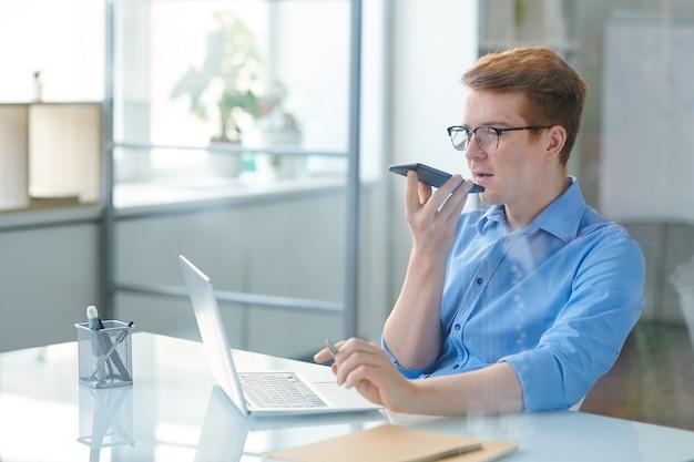 Impiegato contemporaneo che utilizza l'app per messaggi vocali mentre tiene lo smartphone con la bocca