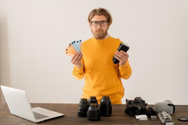 Fotografo contemporaneo che condivide la sua esperienza con il pubblico online durante la lezione che registra nel suo studio fotografico oa casa