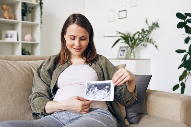 Donna incinta contemporanea che ti mostra l'immagine ultrasonica del futuro bambino e la guarda mentre ti rilassi nell'ambiente domestico