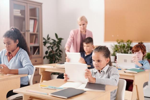 Studentessa contemporanea e i suoi compagni di classe con i touchpad seduti ai banchi e lavorando individualmente mentre l'insegnante sta in piedi accanto a uno di loro