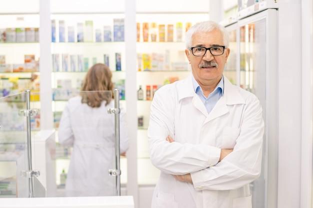 Esperto senior contemporaneo in farmacia e medicina in piedi contro un grande display con prodotti sanitari e ti guarda