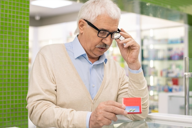 Uomo anziano contemporaneo in occhiali e abbigliamento casual guardando il pacchetto rosso di nuova medicina o additivi biologicamente attivi