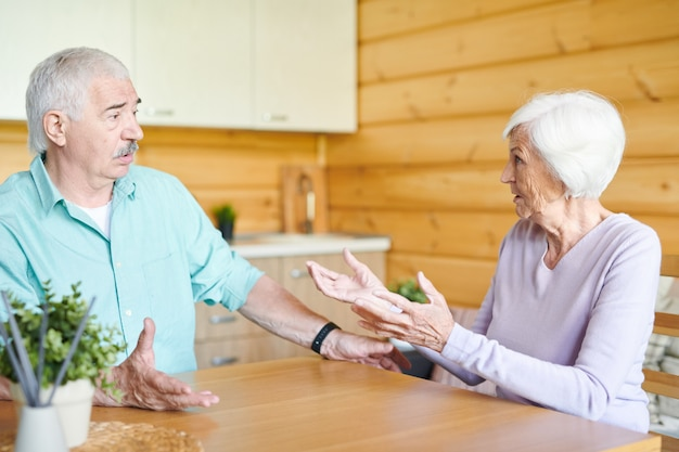 Coniugi senior contemporanei seduti da un tavolo di legno nella cucina della loro casa di campagna e litigando