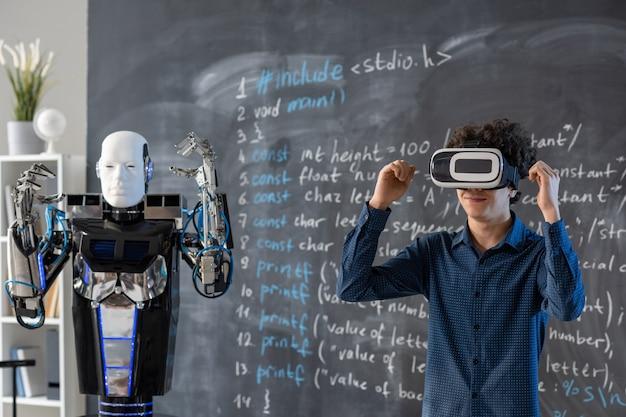 Studente contemporaneo in auricolare vr alzando le mani dalla lavagna mentre fa la presentazione delle abilità del robot durante la lezione