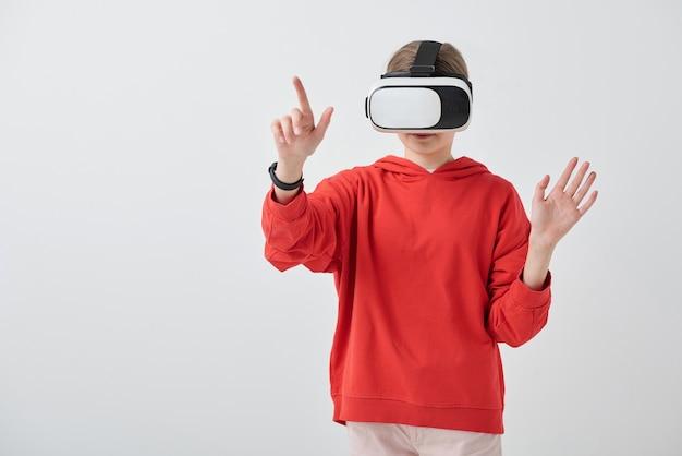 Ragazza adolescente contemporanea in felpa con cappuccio rossa e auricolare vr che punta al display virtuale durante la preparazione o la presentazione