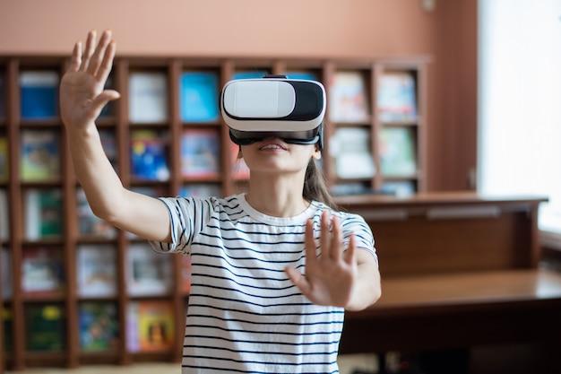 Ragazza adolescente contemporanea con auricolare vr toccando il display virtuale mentre si prepara la presentazione nella biblioteca del college