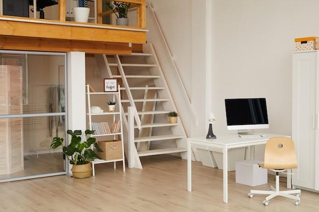 Interni contemporanei di due livelli con home office sul posto di lavoro in primo piano