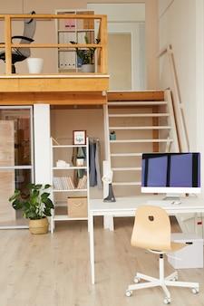 Spazio ufficio contemporaneo a due livelli con scrivania del computer in primo piano