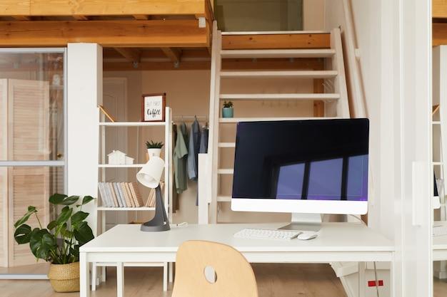 Posto di lavoro contemporaneo in appartamento ufficio a due livelli con scrivania del computer in primo piano
