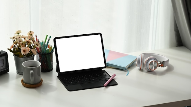 Area di lavoro contemporanea con tablet schermo vuoto, notebook, cuffie, tazza di caffè e vaso di albero sul tavolo bianco.
